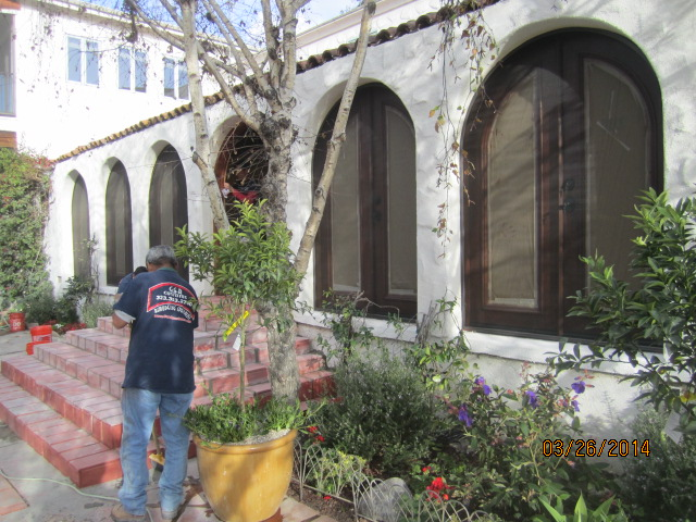 Studio City installation of arched screen panel for inswinging arched oak wood french doors