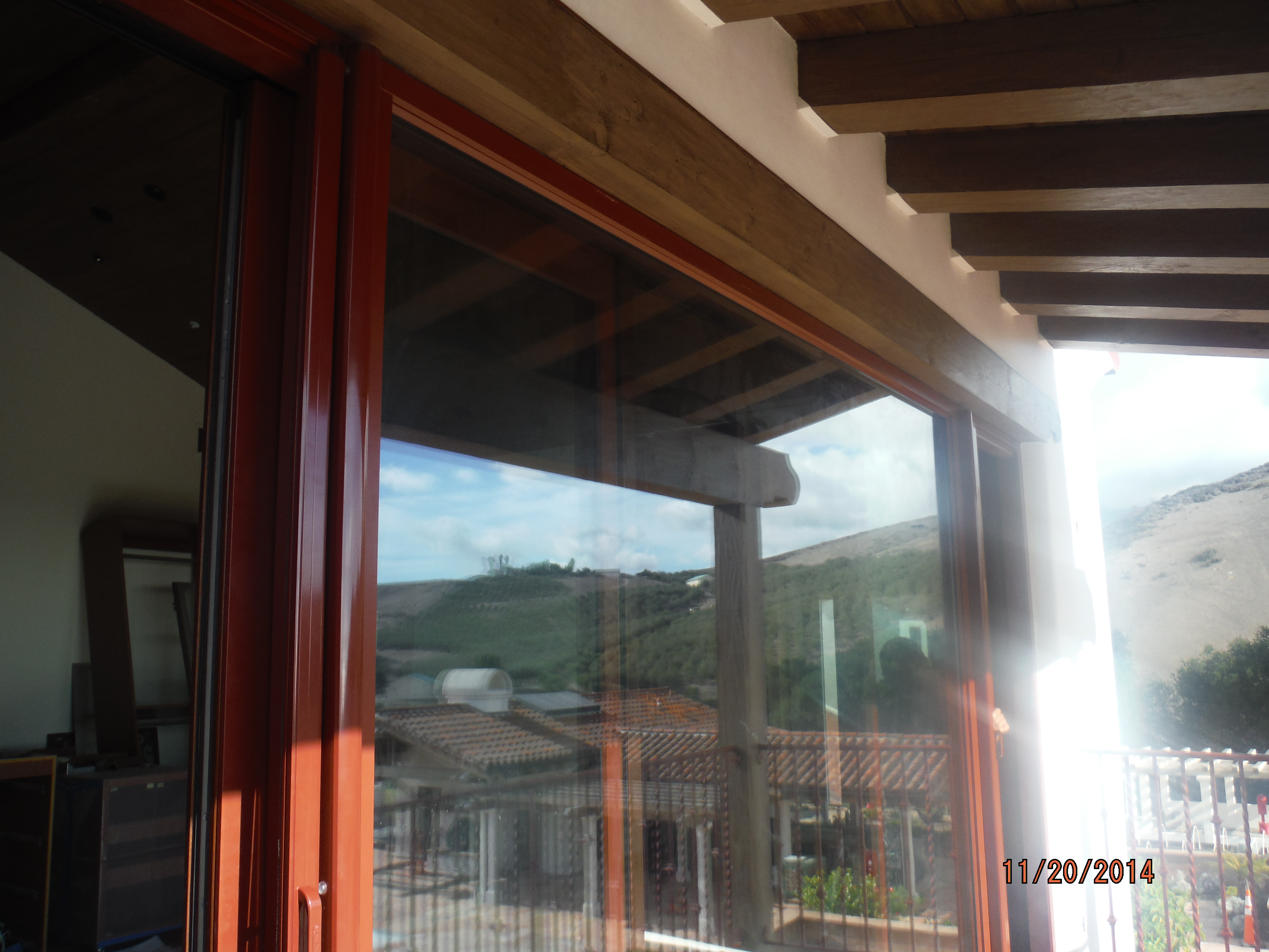 Custom painted and made Mahogany brown/brick retractable screen doors installed on the outside of the front view bi-folding doors for quick ventilation |